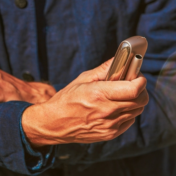 Holder e charger IQOS brilliant gold in una mano maschile