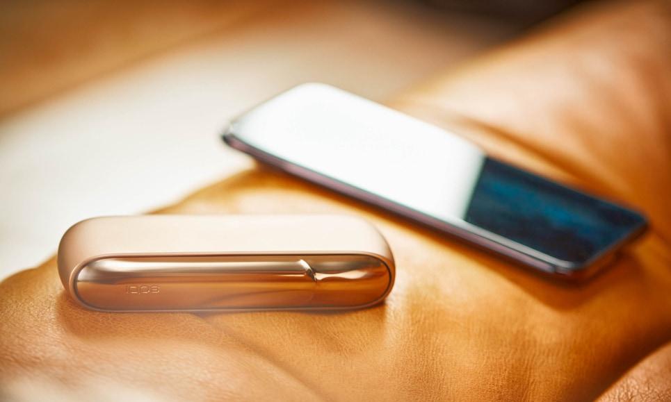 Un IQOS 3 DUO Gold e uno smartphone su un divano