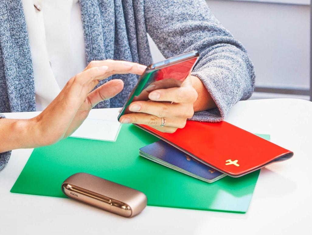 Donna che controlla il telefono con un IQOS sul tavolo