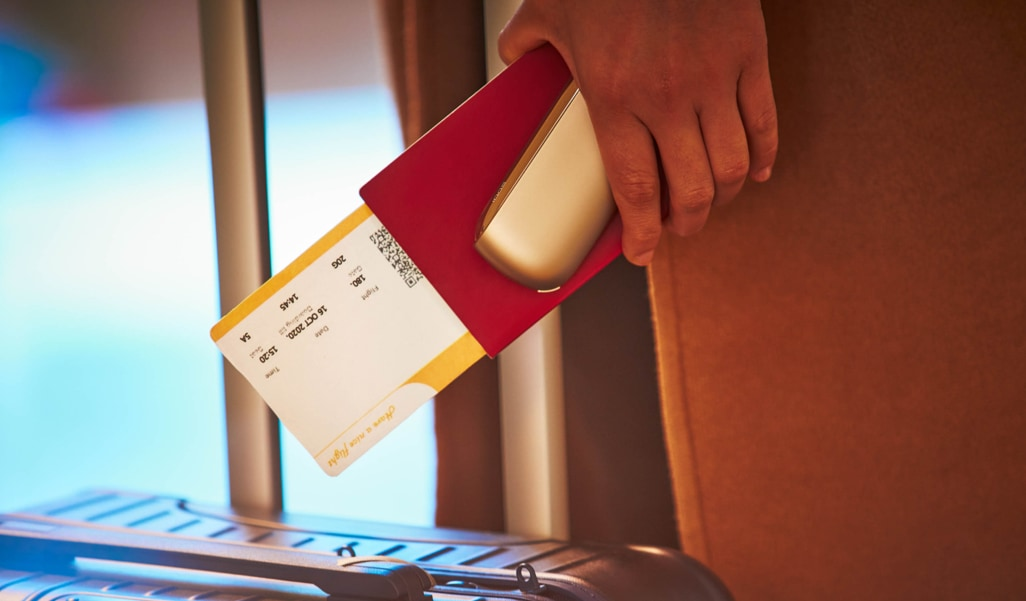 Ragazza con passaporto, biglietto aereo, una valigia e un dispositivo IQOS in mano