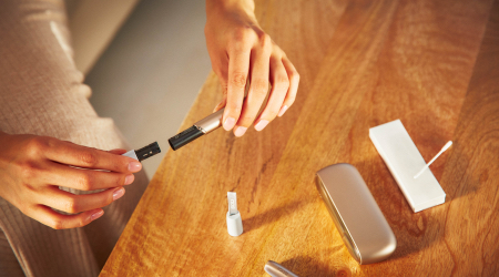 Woman opening her IQOS holder with the charger and other accessories on a table
