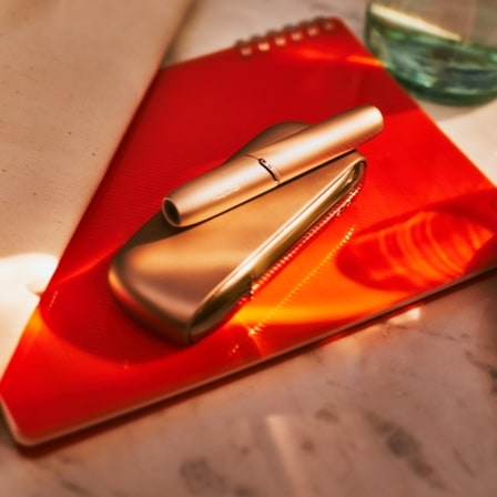 IQOS device on an orange surface