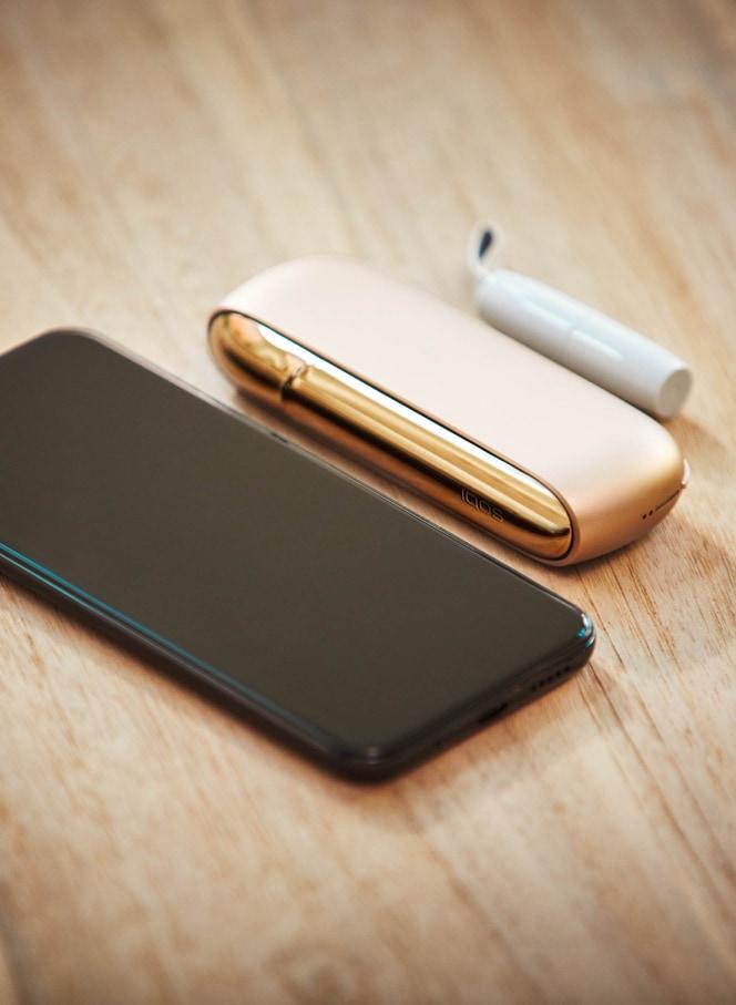 Un cellulare e un kit IQOS Gold su un tavolo