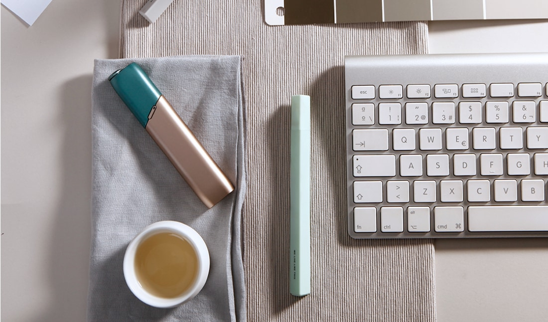 Green and coppery IQOS 3 Multi kit on a working desk