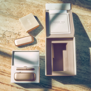 Gold IQOS Duo out of its packaging on a wooden table